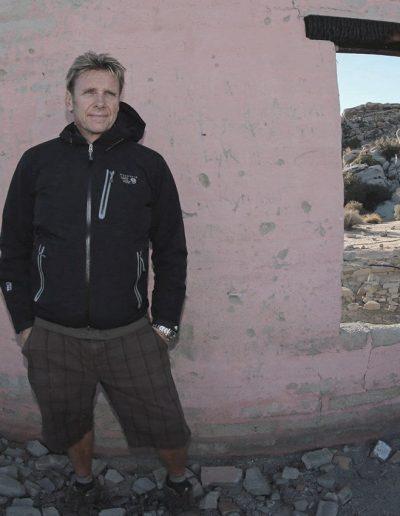 Charlie Webb standing outdoors near an old broken down pink brick wall