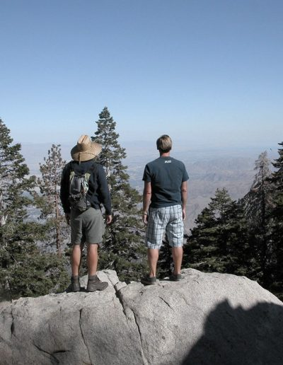 Men hiking standing on a large rock looking at the mountain scene