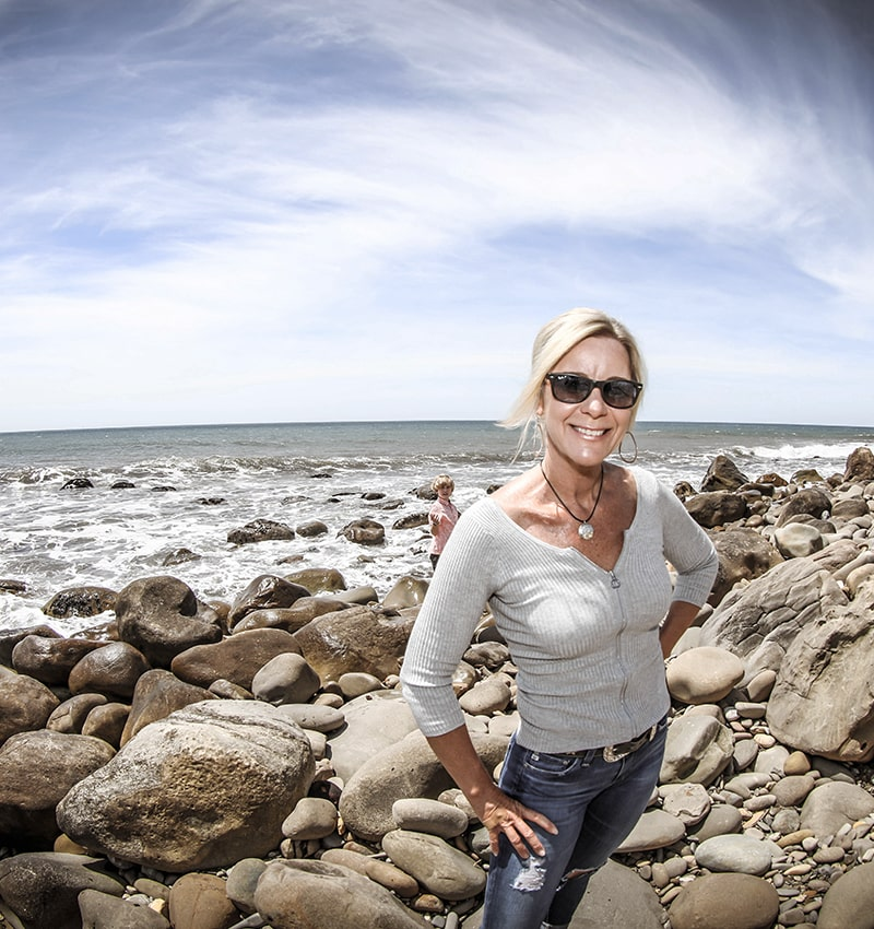 Lisa Wassberg standing on rocks near the ocean
